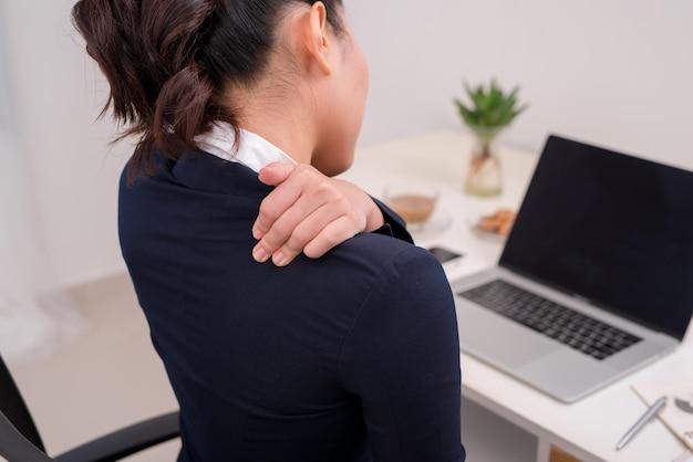 Молодой деловой человек с болью в шее. сосредоточьтесь на руке на шее с ноутбуком на столе в фоновом режиме.