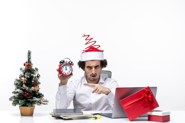 Молодой деловой человек в шляпе санта-клауса и держит часы и указывает что-то в офисе на белом фоне