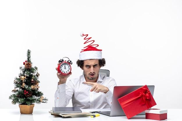Giovane uomo d'affari con cappello di babbo natale e tenendo l'orologio e indicando qualcosa in ufficio su sfondo bianco