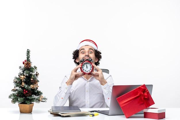 Giovane uomo d'affari con il cappello di babbo natale e mostrando l'orologio guardando qualcosa con attenzione e seduto in ufficio su sfondo bianco