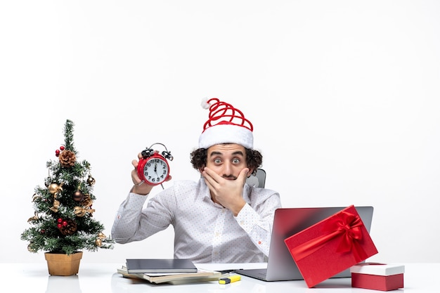 Young business person with santa claus hat and showing clock thinking about something carefully and sitting in the office on white background