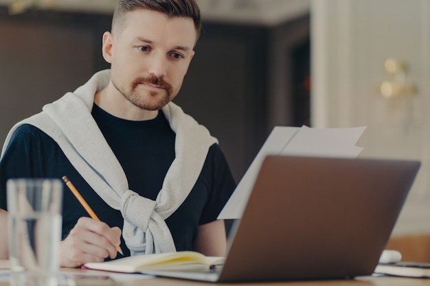 Young business professional or male freelancer looking at laptop screen and making some notes while sitting behind work desk in light office or home. job occupation and freelance concept