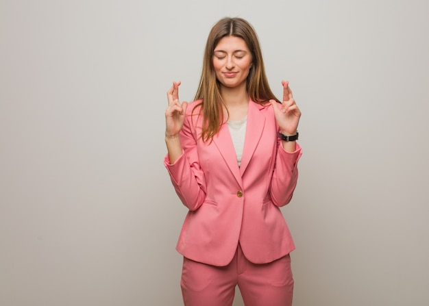 Young business russian girl crossing fingers for having luck