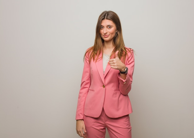 Young business russian girl smiling and raising thumb up