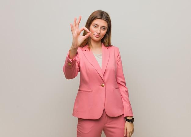 Молодой бизнес русская женщина веселая и уверенно делает хорошо жест