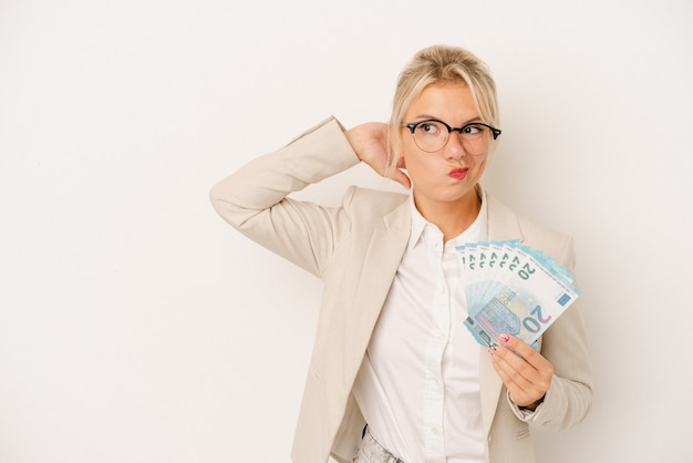 頭の後ろに触れて、考えて、選択をする白い背景で隔離の紙幣を保持している若いビジネスロシアの女性。