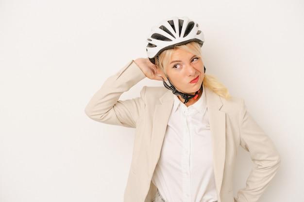 頭の後ろに触れて、考えて、選択をする白い背景で隔離の自転車のヘルメットを保持している若いビジネスロシアの女性。