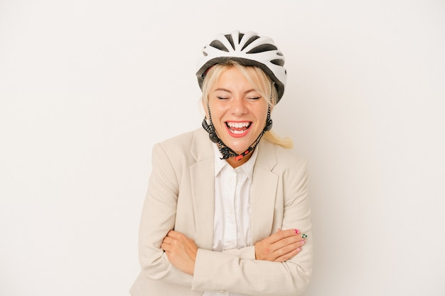 Young business russian woman holding bike helmet isolated on white background laughing and having fun.
