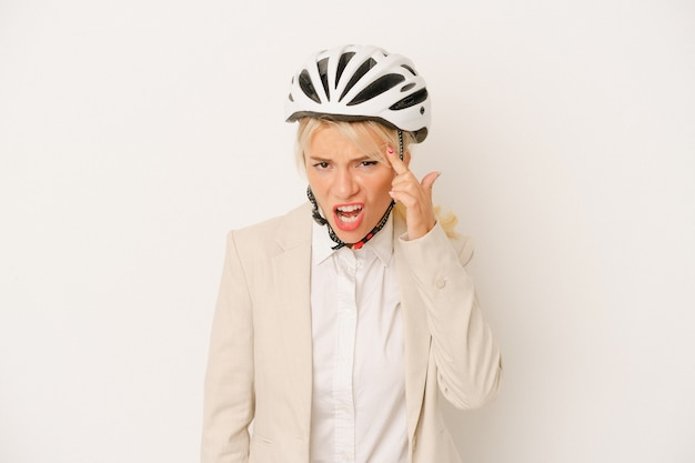Young business russian woman holding bike helmet isolated on white background showing a disappointment gesture with forefinger.