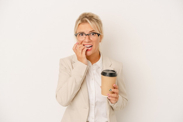 Young business russian woman holding take away coffee isolated on white background biting fingernails, nervous and very anxious.