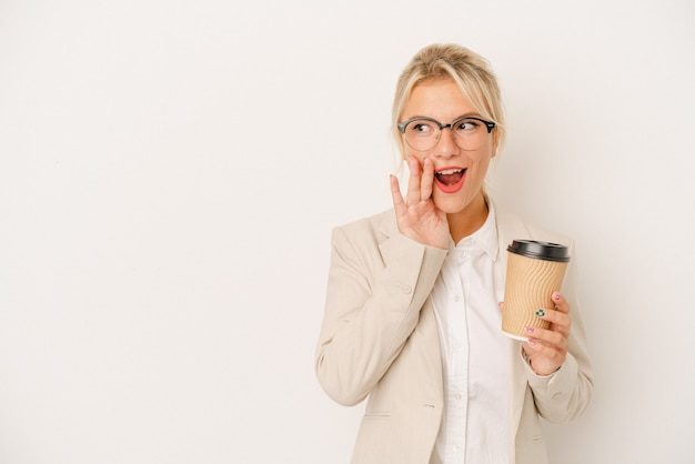 Young business russian woman holding take away coffee isolated on white background is saying a secret hot braking news and looking aside