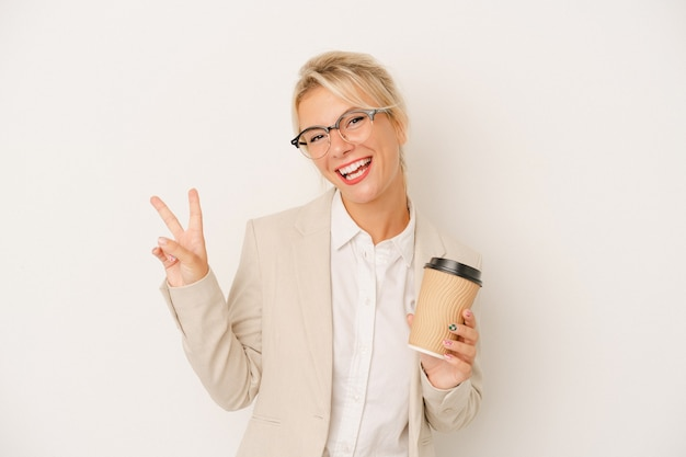 Young business russian woman holding take away coffee isolated on white background joyful and carefree showing a peace symbol with fingers.