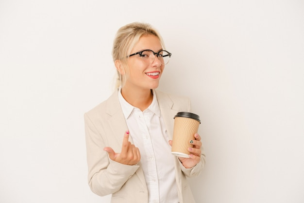 Young business russian woman holding take away coffee isolated on white background pointing with finger at you as if inviting come closer.