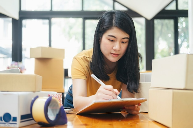 Young business startup online seller owner using computer for checking the customer orders from email or website and preparing packages for product office equipment.