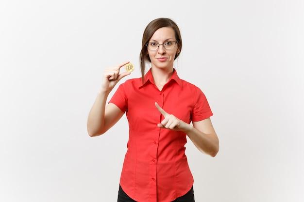 빨간 셔츠를 입은 젊은 비즈니스 교사 여성, 비트코인을 들고 있는 안경, 흰색 배경에 격리된 황금색 금속 동전. 미래 통화, 교육 성취 경력 재산 개념. 여사장님.