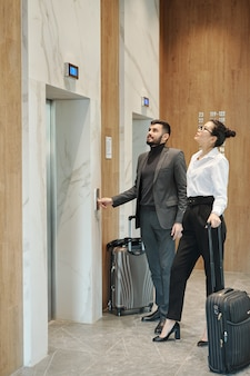 Young business travelers with baggage standing by one of elevator doors in hotel and looking at countdown panel above