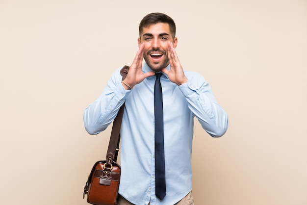 Young business with beard over isolated background shouting with mouth wide open