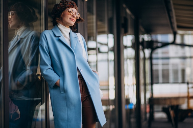 Young business woman in blue coat by the cafe