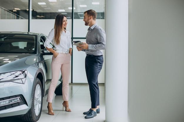車のショールームで車を買う若いビジネスウーマン