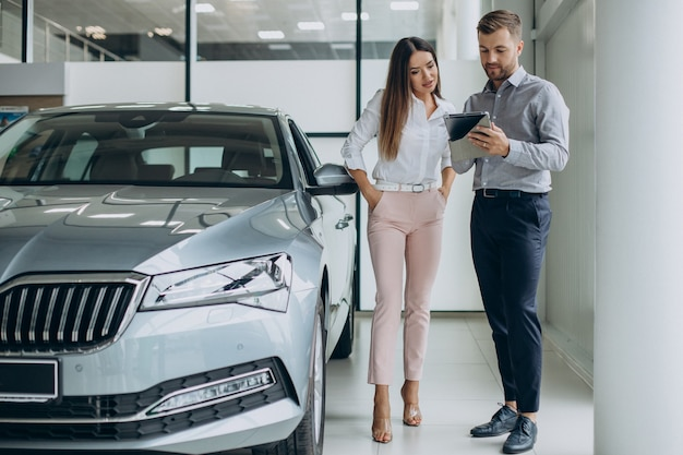 Young business woman buying a car in car showroom