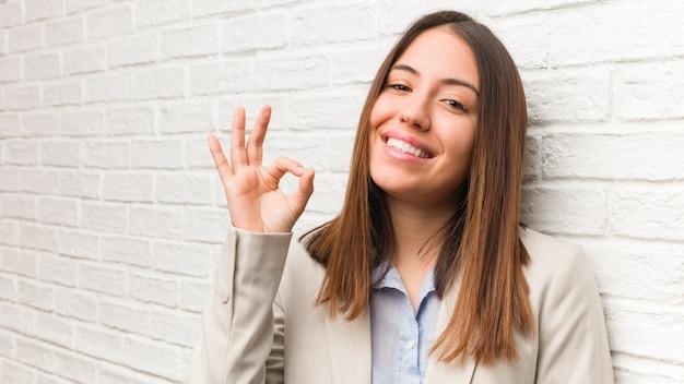 Молодая деловая женщина, веселая и уверенная в себе, делает хорошо жест
