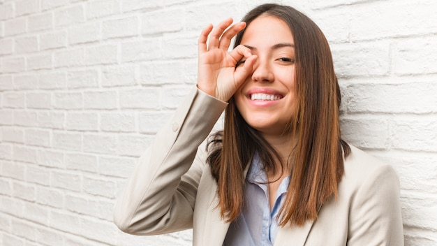 Young business woman confident doing ok gesture on eye