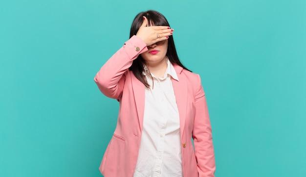 片手で目を覆っている若いビジネスウーマンは、恐怖や不安を感じ、不思議に思ったり、盲目的に驚きを待っています