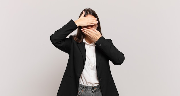 Young business woman covering face with both hands saying no to the camera! refusing pictures or forbidding photos