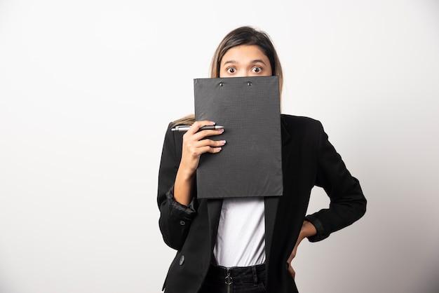 白い壁にクリップボードで彼女の顔を覆う若いビジネス女性
