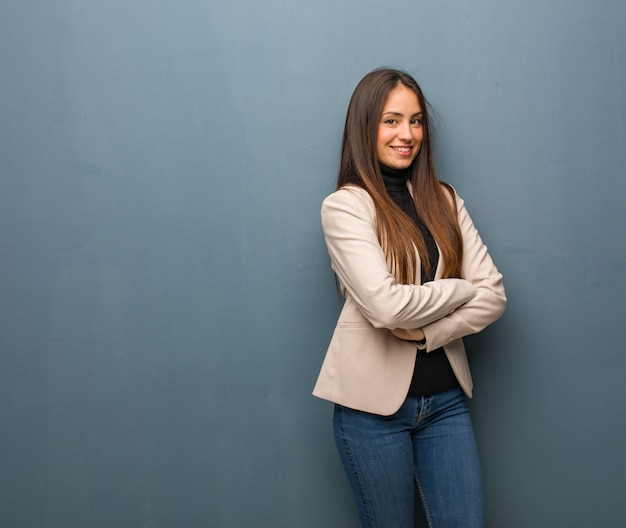 Young business woman crossing arms, smiling and relaxed