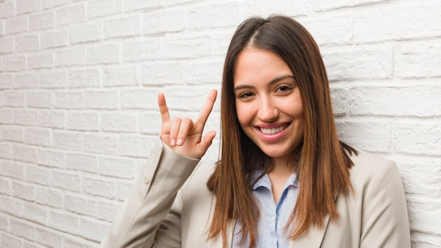 Young business woman doing a rock gesture