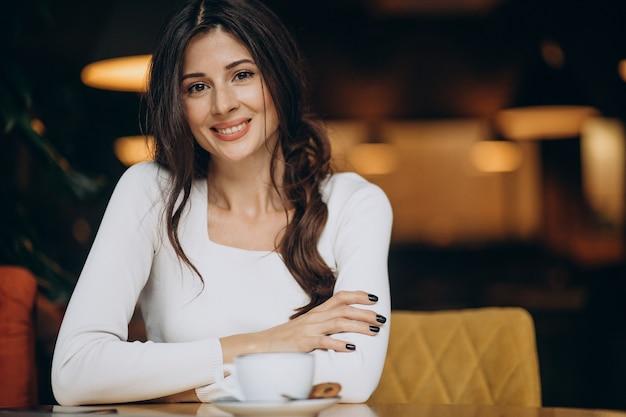 Giovane donna di affari che beve il caffè in un caffè