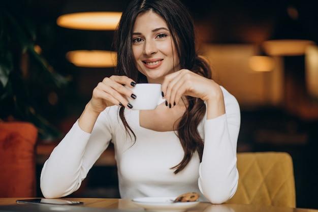 Молодая деловая женщина пьет кофе в кафе