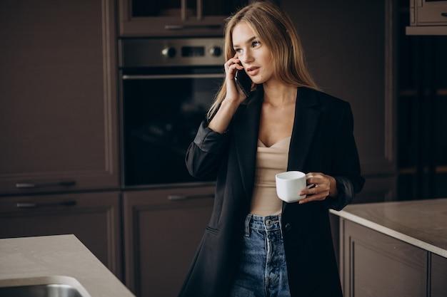 Giovane donna di affari che beve caffè e parla al telefono in cucina