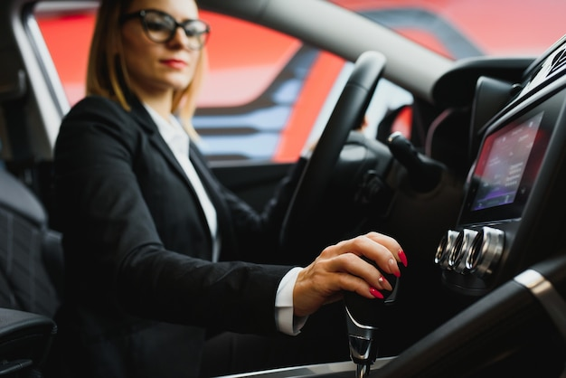 Young business woman driving in her car to work.