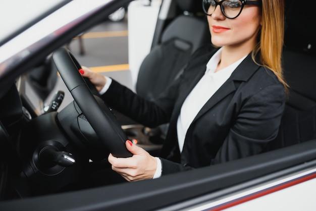 그녀의 차에서 운전하는 젊은 비즈니스 우먼.