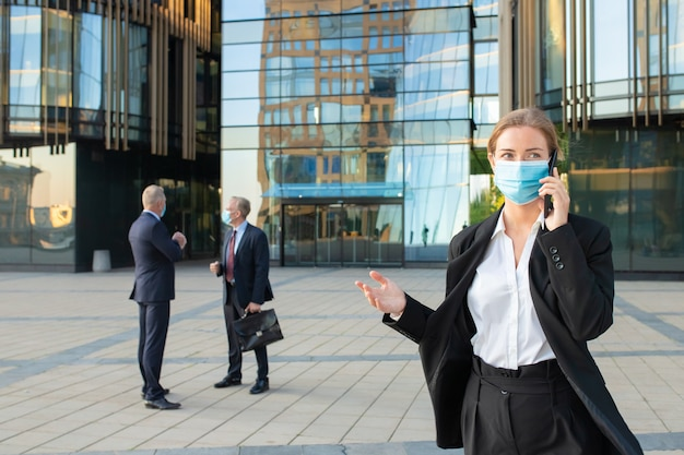 Young business woman in face mask and office suit talking on mobile phone outdoors. businesspeople and city buildings in background. copy space. business and epidemic concept