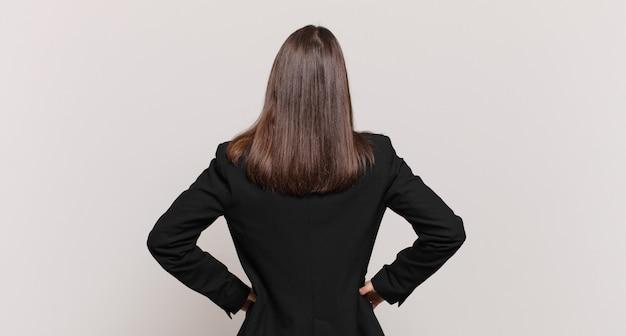 젊은 비즈니스 여성은 혼란스럽거나 가득 차거나 의심과 질문을 느끼고, 엉덩이에 손을 대고, 후면을 봅니다.