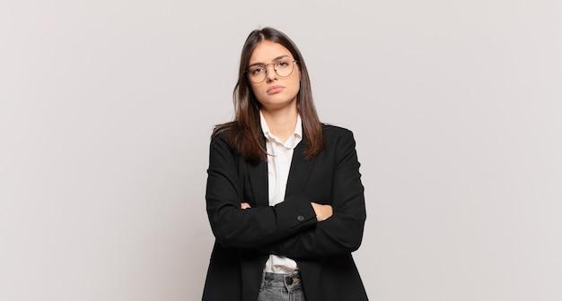 젊은 비즈니스 여성은 불쾌하고 실망하며 팔짱을 끼고 진지하고 짜증이 나고 화난 표정을 짓고 있습니다.