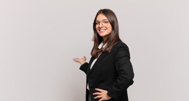 젊은 비즈니스 여성은 행복하고 쾌활하며 웃고 환영하며 친근한 몸짓으로 당신을 초대합니다.