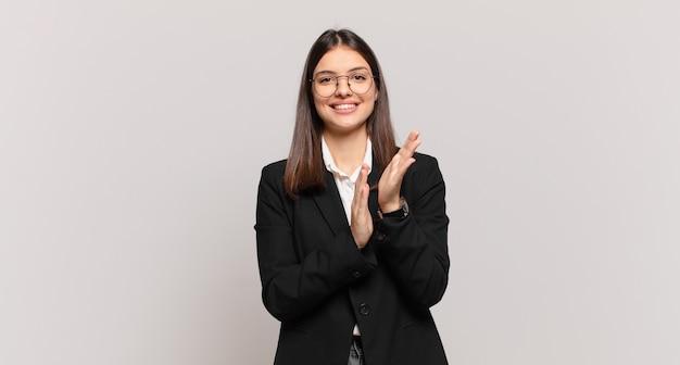 행복하고 성공적인 느낌을 주는 젊은 비즈니스 여성, 미소 짓고 박수를 치며 박수로 축하합니다