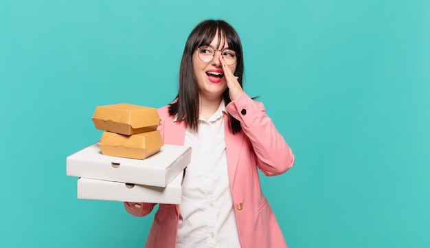 젊은 비즈니스 여성은 행복하고 흥분되며 긍정적인 감정을 느끼며 손을 입 옆에 대고 큰 소리로 외치고 있습니다.