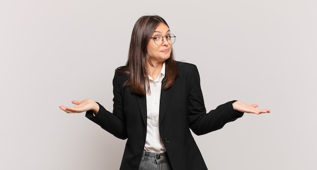 Young business woman feeling puzzled and confused, unsure about the correct answer or decision, trying to make a choice