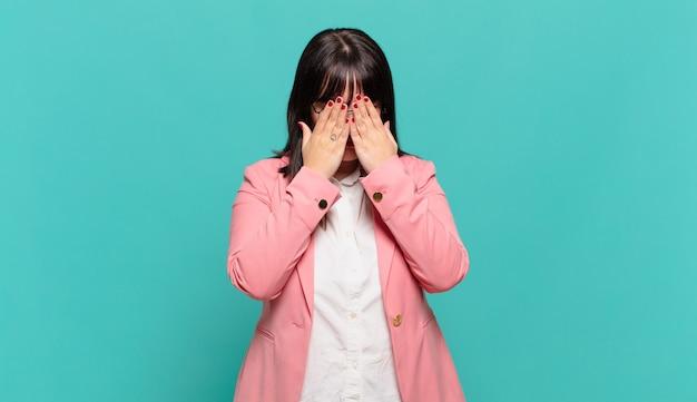 슬프고, 좌절하고, 긴장하고, 우울하고, 양손으로 얼굴을 덮고, 울고있는 젊은 비즈니스 우먼