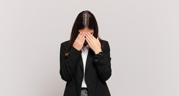 젊은 사업가는 슬프고, 좌절하고, 긴장하고, 우울하고, 두 손으로 얼굴을 가리고, 울고 있다