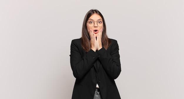Молодая деловая женщина чувствует себя потрясенной и напуганной, выглядит испуганной с открытым ртом и руками по щекам