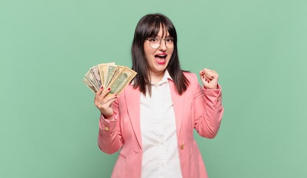 젊은 비즈니스 여성은 충격을 받고 흥분되고 행복하며 웃고 성공을 축하하며 와우!