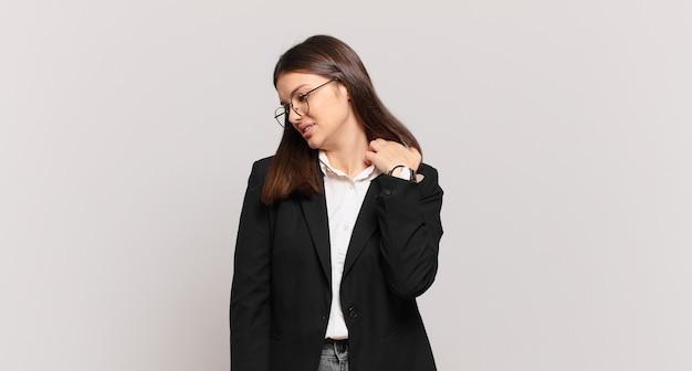 Молодая деловая женщина чувствует стресс, тревогу, усталость и разочарование, тянет рубашку за шею, выглядит разочарованной из-за проблемы