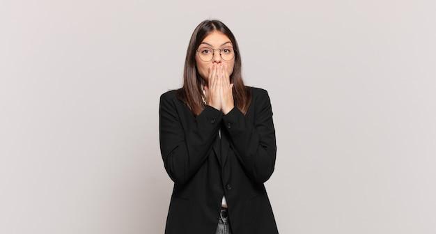 젊은 비즈니스 여성은 걱정하고, 화가 나고, 무서워하고, 손으로 입을 가리고, 불안해 보이고, 엉망이 되었습니다.