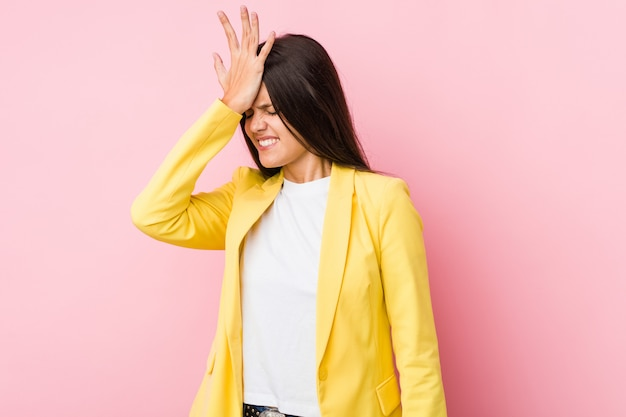 Young business woman forgetting something, slapping forehead with palm and closing eyes.